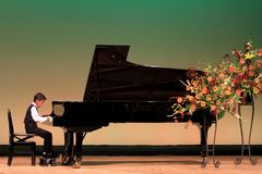 Japanese boy playing piano on stage Royalty Free Stock Images
