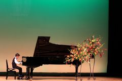 Japanese boy playing piano on stage Stock Images