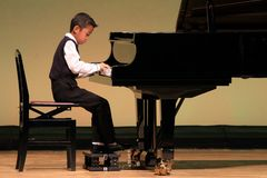 Japanese boy playing piano on stage Stock Photo