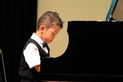 Japanese boy playing piano Stock Image