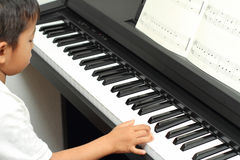 Japanese boy playing a piano Royalty Free Stock Photos