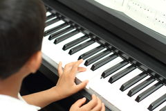 Japanese boy playing a piano. (5 years old stock photo