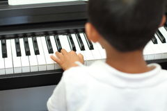 Japanese boy playing a piano. (5 years old royalty free stock photos