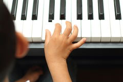 Japanese boy playing a piano. (5 years old royalty free stock photo