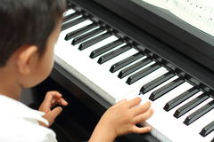 Japanese boy playing a piano. (5 years old royalty free stock image
