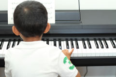 Japanese boy playing a piano Stock Image