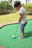 Japanese boy playing with putting golf Stock Photo