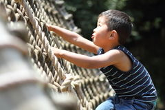 Japanese boy playing with rope ladder Stock Photos