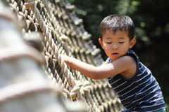 Japanese boy playing with rope ladder Stock Photo