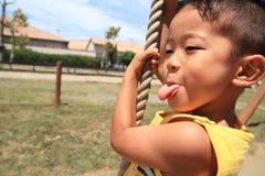 Japanese boy playing with Tarzan rope Stock Photos