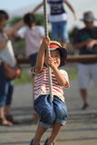 Japanese boy playing with Tarzan rope Stock Images