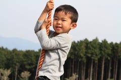Japanese boy playing with Tarzan rope Stock Image