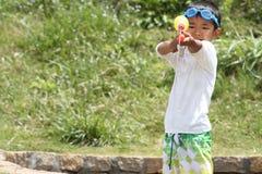 Japanese boy playing with water gun Royalty Free Stock Photo