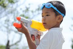 Japanese boy playing with water gun. (first grade at elementary school royalty free stock photography