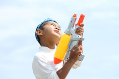 Japanese boy playing with water gun Stock Images
