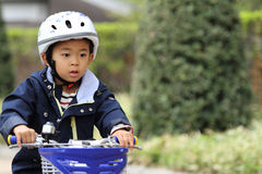 Japanese boy riding on the bicycle Royalty Free Stock Photo