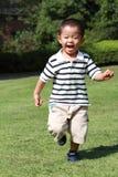 Japanese boy running on the grass in summer. Japanese boy running on the grass 3 years old in summer Stock Photos
