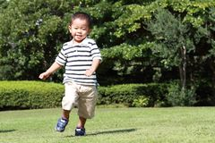 Japanese boy running on the grass in summer. Japanese boy running on the grass 3 years old in summer Stock Image