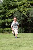 Japanese boy running on the grass in summer. Japanese boy running on the grass 3 years old in summer Royalty Free Stock Photo