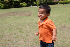 Japanese boy running on the grass Royalty Free Stock Photography