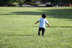 Japanese boy running on the grass Stock Photo