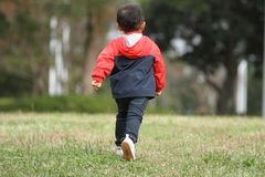 Japanese boy running on the grass. 3 years old Royalty Free Stock Image