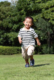 Japanese boy running on the grass Royalty Free Stock Photo