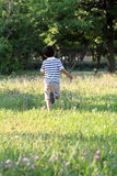 Japanese boy running on the grass Stock Image