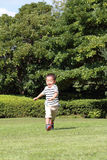 Japanese boy running on the grass Royalty Free Stock Images