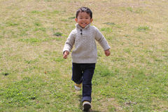 Japanese boy running on the grass Stock Images