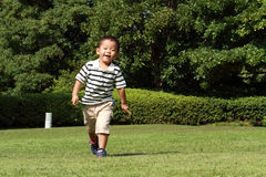 Japanese boy running on the grass Royalty Free Stock Image