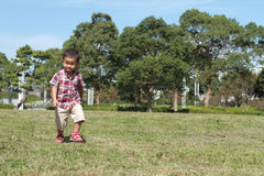 Japanese boy running on the grass Royalty Free Stock Photos