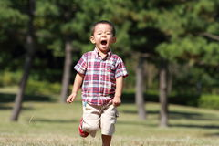 Japanese boy running on the grass Stock Photography