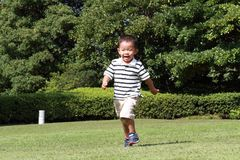 Japanese boy running on the grass in summer. Japanese boy running on the grass 3 years old in summer Royalty Free Stock Photos