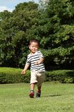 Japanese boy running on the grass in summer. Japanese boy running on the grass 3 years old in summer Royalty Free Stock Photography