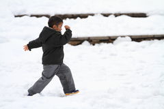 Japanese boy running on the snow field Royalty Free Stock Image