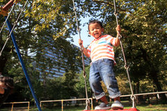 Japanese boy on a swing Stock Images