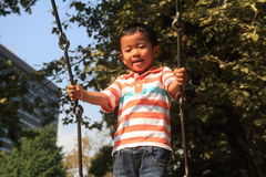 Japanese boy on a swing Stock Image