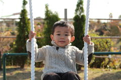 Japanese boy on the swing Royalty Free Stock Images
