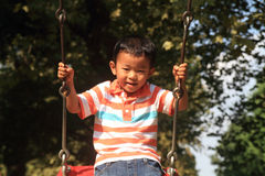 Japanese boy on a swing Stock Photo
