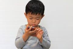 Japanese boy using smart phone Royalty Free Stock Images