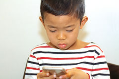 Japanese boy using a smart phone Stock Images