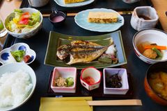 Japanese breakfast dishes including cooked white rice, grilled fish, fried egg, miso soup, royalty free stock photo