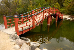Japanese Bridge. Over a small pond adds aesthetic touch to a quiet scene stock images