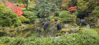 Japanese Bronze Cranes Sculpture by Pond Stock Photo