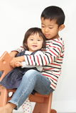 Japanese brother and sister playing with rocking horse Stock Images