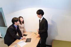 Japanese business woman and men talking at desk, with tablet device Stock Photo