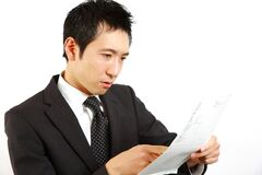 Japanese businessman checks document. Concept shot of Japanese businessman Stock Photo