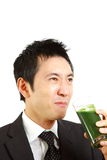 Japanese businessman with green vegetable juice Royalty Free Stock Photography