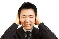 Japanese businessman holding hands on his ears, protecting himself from noise Stock Photo